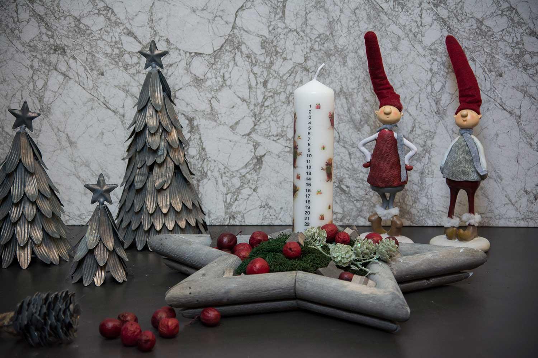 Kalenderlys og juledekoration med juletræer og nisser.