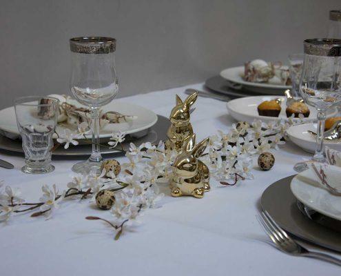 Hvidt påskebord med gyldne påskeharer og orkideranker