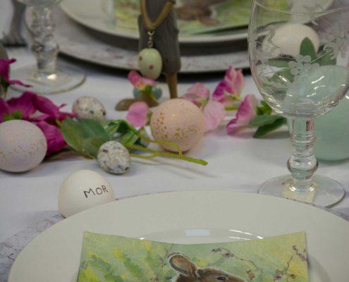 Påskebord med påskeharer og farverige påskeæg