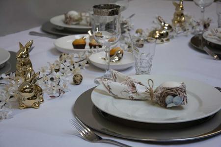 Påskebord med sølvtallerkener og gyldne påskeharer
