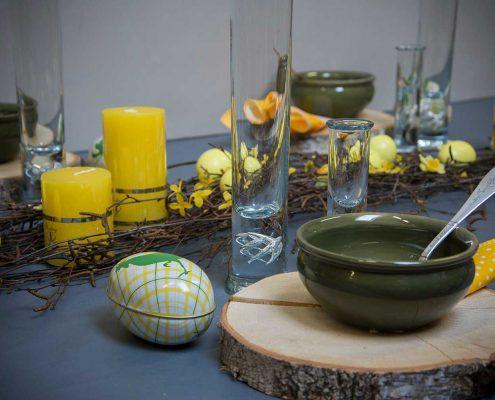Påskebord med træskiver, birkegrene og gule påskeæg