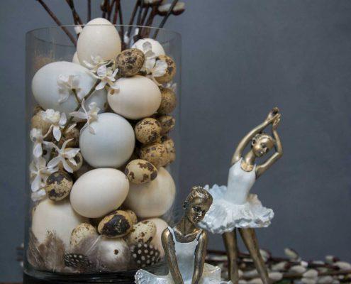 Påskedekoration - glas vase fyldt med påskeæg og gæslinge grene