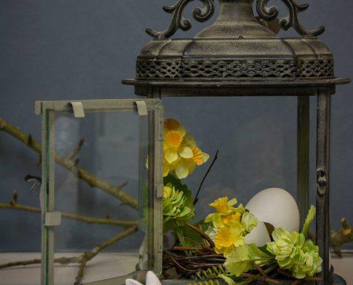 Påskedekoration med gule påskeliljer og påskeæg i lanterne