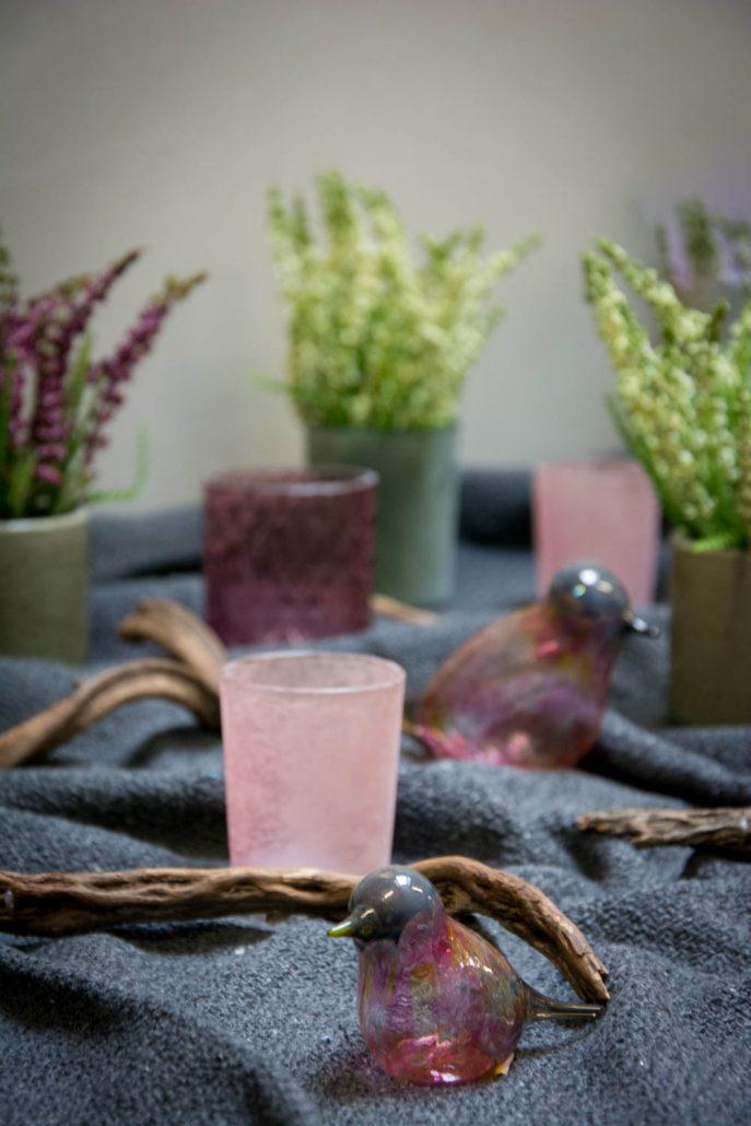 Blommefarvet bordpynt med lyng og glasfugle