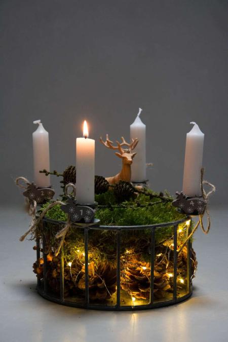 Adventsdekoration i adventsstage på bund af kogle og lyskæde.