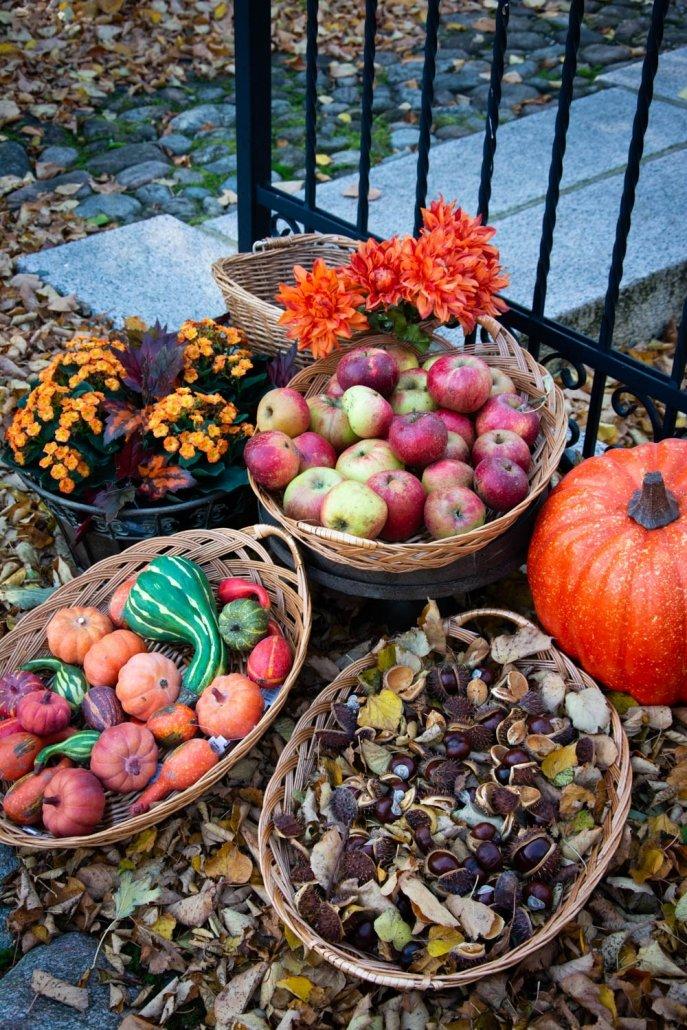 Udendørs efterårsdekorationer med æbler, kastanjer og pyntegræskar
