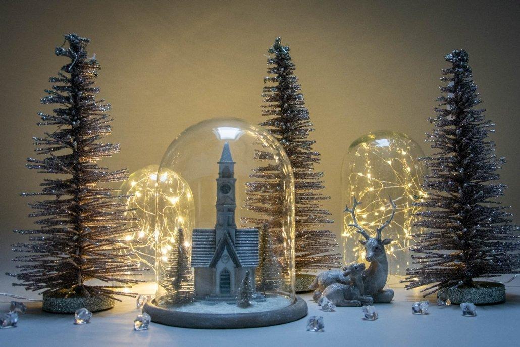 Julepynt i glasklokke med gyldne juletræer omkring