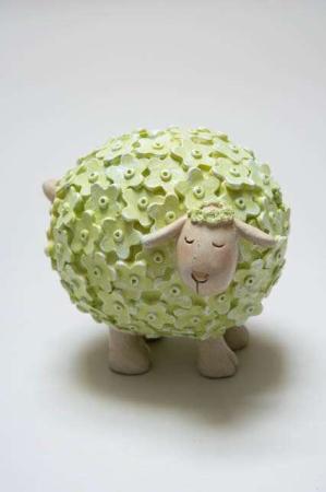 Blomstret får af keramik. Grønt påskelam med blomster
