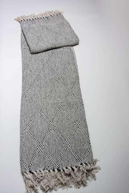 Harlekinmønstret tæppe i bomuld. Tæppe med harlekinmønster. Sort og hvidt tæppe med frynser.