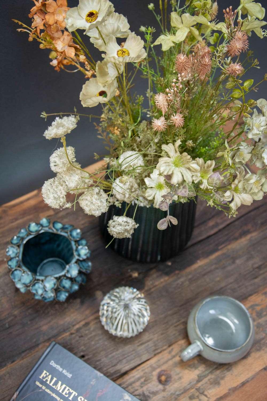 Kunstige tørrede blomster i farvet glasvase