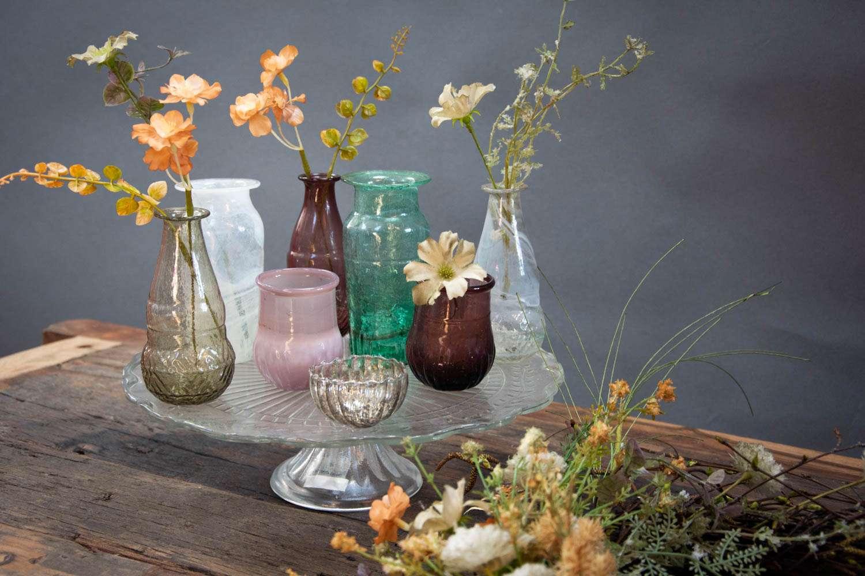 Små glasvaser i farvet glas med kunstige blomster