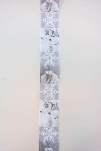 Hvidt dekorationsbånd med slædehunde og snefnug. Bredt julebånd til juledekorationer og julegaver.
