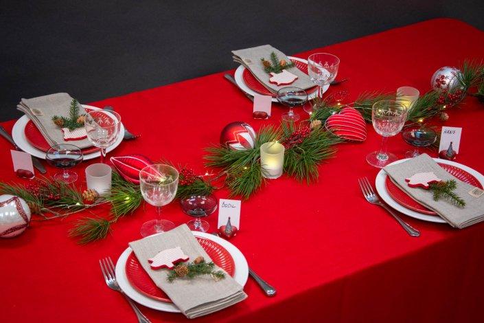 Inspiration til julebord med rød juledug, gran og julekugler